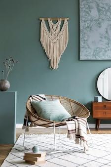 籐のアームチェア、家具、壁に格子縞のベージュのマクラメ、花、エレガントなアクセサリーを備えたリビングルームのスタイリッシュなミニマルなインテリア