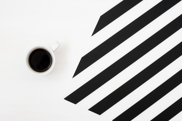 Stylish minimalistic workspace with cup of coffee on striped background