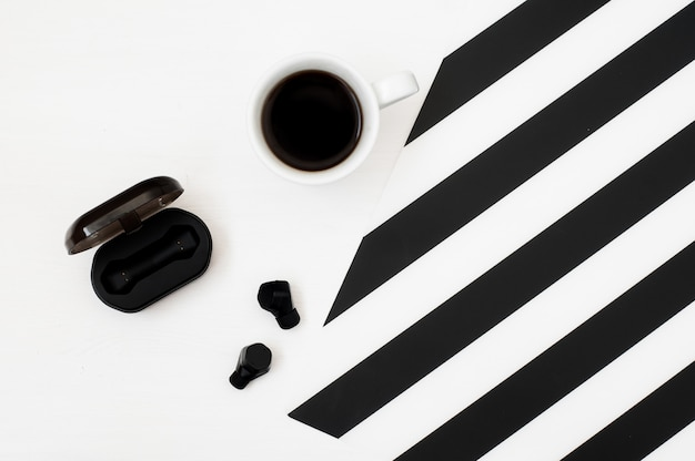 Stylish minimalistic workspace with cup of coffee, wireless earphones