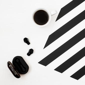 スタイリッシュなミニマルワークスペース。コーヒー、ワイヤレスイヤホン