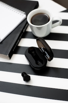 Stylish minimalistic workspace with mock up notebook, pencil, cup of coffee, wireless earp
