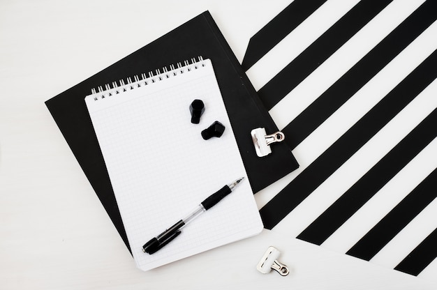 Stylish minimalistic workspace with mock up notebook, pencil, wireless earphones