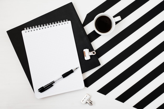 Stylish minimalistic workspace with notebook mock up, pencil and cup of coffee