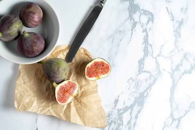 大理石の壁にクラフト紙にイチジクをカットしてスタイリッシュなモックアップ。平らな果物を食べる準備ができています。夏の甘い果実。イチジクのボウル。コピースペース。食物。上面図