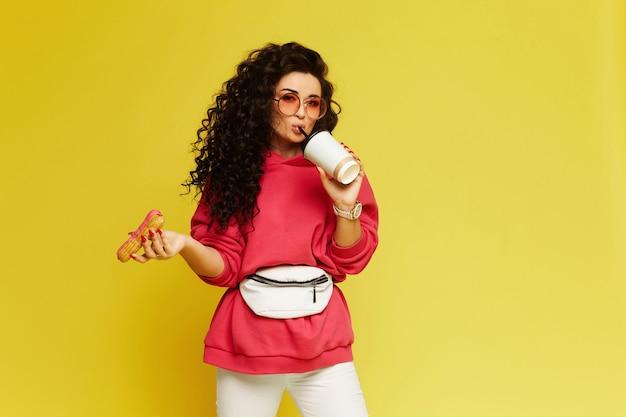 行くためにコーヒーカップと黄色の壁に分離されたおいしいデザートを保持しているピンクのパーカーのスタイリッシュなモデルの女の子、コピースペースでスタジオ撮影