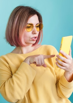 Stylish model pointing at phone