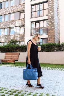 새로운 옷 컬렉션에서 포즈를 취하는 가방과 커피 컵이 달린 안경을 쓴 검은 드레스를 입은 세련된 모델 여성