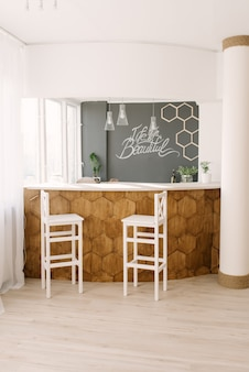 A stylish modern bar counter decorated with wooden tiles and two white bar stools in the living room of the house. scandinavian interior design