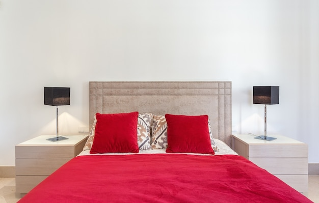 Stylish modern bedroom with bed and red pillows.