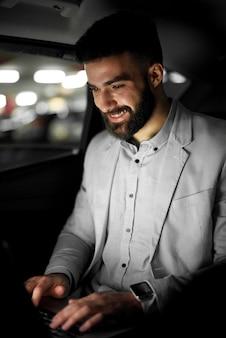 スタイリッシュなモダンなビジネスマンが車で働いています。