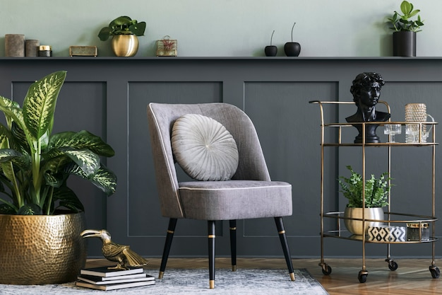 Stylish and modern composition of living room with design gray armchair, gold liquor cabinet, plants and elegant personal accessories. gray wall panelling with shelf. modern home decor.