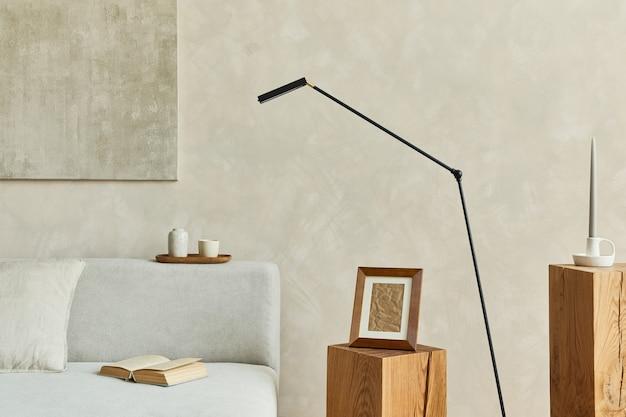 모의 포스터 프레임, 회색의 우아한 소파, 나무 큐브, 미니멀한 램프 및 개인 액세서리를 갖춘 거실 인테리어의 세련되고 현대적인 구성. 중성 색상. 주형.