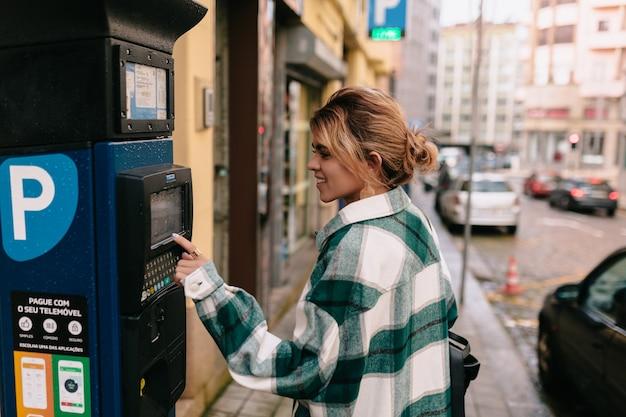 Elegante ragazza moderna con capelli biondi raccolti in viaggio. ritratto all'aperto di giovane donna sorridente timida che cammina nella città vecchia