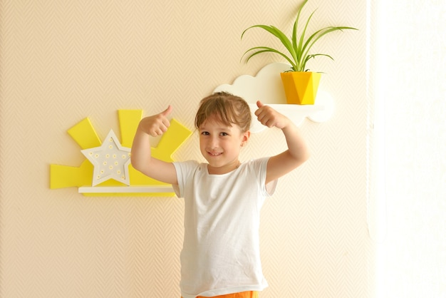 Stylish and modern interior design. girl happy lifestyle in the nursery new shelves. children's shelves in the form of white clouds on a plain beige wall, on which there is a yellow pot with a flower.