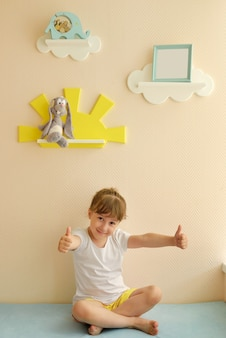 Stylish and modern interior design. home for the child room. the child rejoices in the renewed room. children's shelves in the form of white clouds on a plain beige wall with a photo frame.