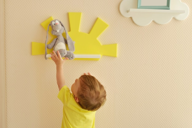 Stylish and modern interior design. home for the child room. todder boy takes a gray hare's soft toy from the shelf.