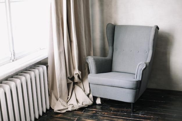 창가에 아늑한 안락 의자가있는 세련되고 현대적인 인테리어 디자인.