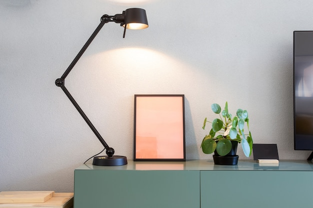 Stylish modern interior, empty picture frame with black lamp and green chinese money plant, retro pancake plant on green table scandinavian design