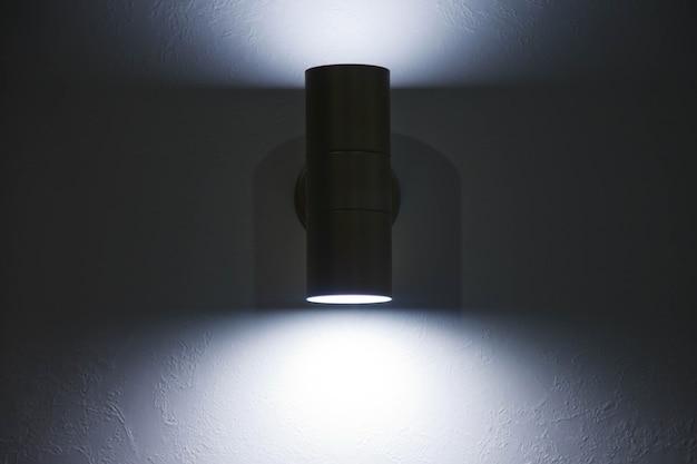 白い織り目加工の壁にスタイリッシュでモダンなランプ。灰色の壁に輝くクロムledランプ。碑文の背景に空き領域と暗いストライプ。サイトまたはバナーの著作権スペース