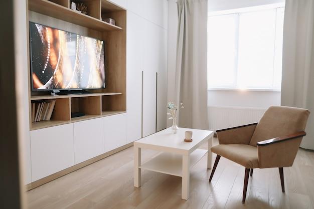 Tv, 안락 의자, 커피 테이블 및 커튼이있는 창문을 갖춘 세련되고 현대적인 거실 인테리어 디자인입니다.