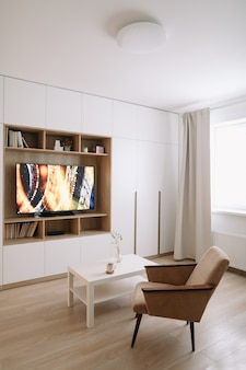 Stylish modern living room interior design with tv, armchair, coffee table and a window with curtains.