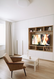 Стильный современный интерьер гостиной с телевизором, креслом, журнальным столиком и окном с занавесками