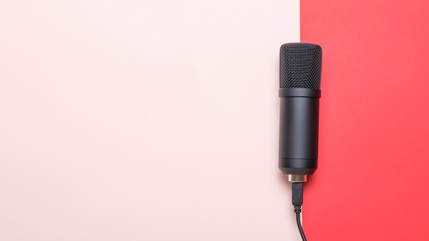 Stylish modern microphone on red and pink surface. sound recording equipment.