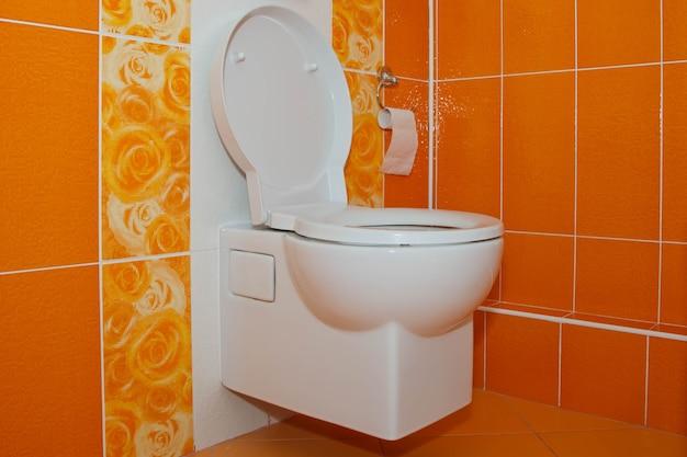샤워실에 주황색 장식 타일이 있는 세련된 현대적인 화장실입니다. 디자인 디자인의 개념 또는 인간의 요구에 대처합니다. 사이트 또는 배너의 저작권 공간