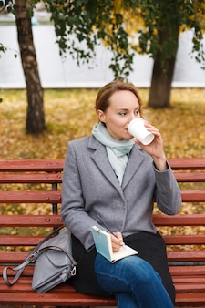 Stylish modern woman in elegant clothes sitting drinking coffee and writing something in notebook
