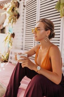 Стильная современная женщина с собранными светлыми волосами, расслабляющаяся на открытом воздухе в солнечный теплый день