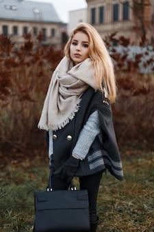 가죽 패션 가방이 달린 검은 청바지에 스카프가 달린 검은 코트에 회색 니트 스웨터에 세련된 현대 젊은 여성이 도시의 마른 잔디 근처에 서 있습니다. 매력적인 소녀.