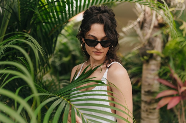 Stylish modern young woman with blond curly hairstyle wearing summer clothes walking among tropics in summer sunny day. outside photo of happy smiling girl has fun and enjoying weekend