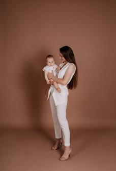 Стильная мама и дочь ребенка на бежевом фоне с местом для текста