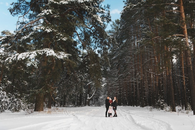 Stylish mom, dad, daughter and little son are walking in the winter forest. the family has a good time together. view from afar. selective focus