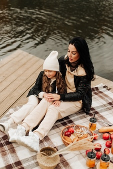 Stylish mom and daughter at the autumn picnic sit on a blanket near the water
