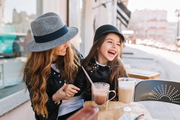 Stylish mom and pretty smiling daughter enjoying weekend together in outdoor restaurant drinking coffee and milk shake.