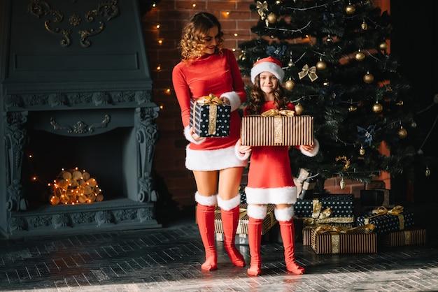 Стильная мама с маленькой дочкой в рождественских костюмах возле елки. счастливого рождества.
