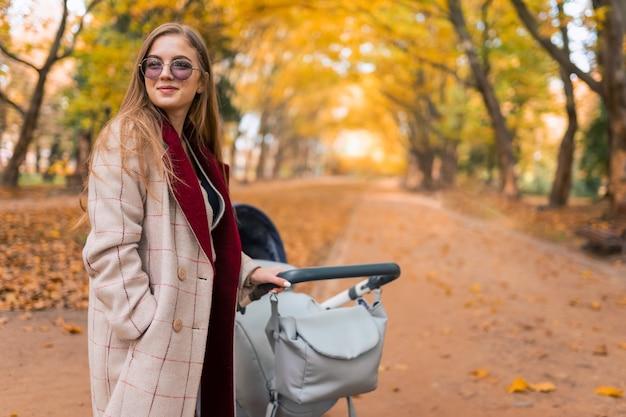 秋の公園でベビーカーとスタイリッシュなママ