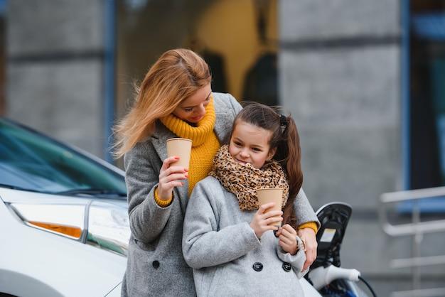 Стильные мама и дочка заряжают электромобиль и проводят время вместе