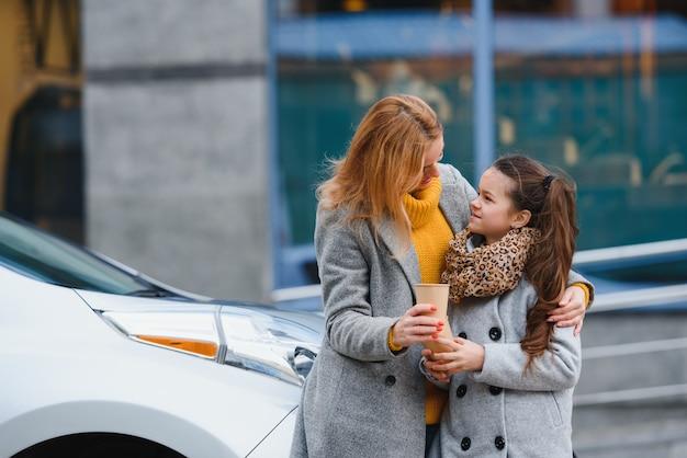 Стильные мама и дочка заряжают электромобиль и проводят время вместе Premium Фотографии
