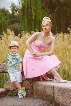 スタイリッシュな母と息子の外でポーズ
