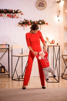 Stylish mother playing with baby boy in santa hat sitting on floor near christmas decorations