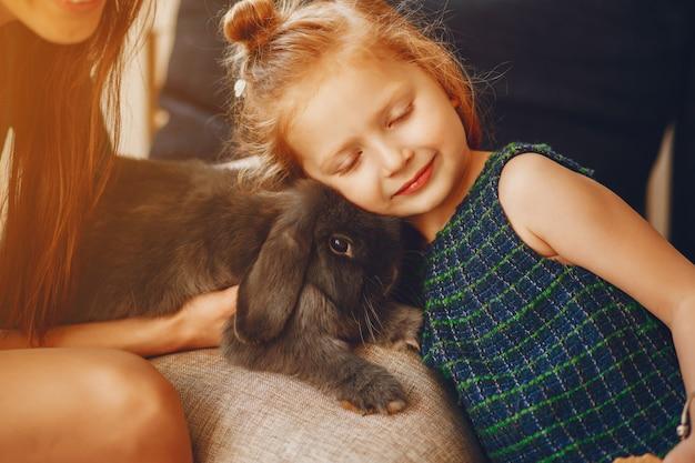 彼女の小さなかわいい娘と遊んで長い髪と緑のドレスとスタイリッシュな母親