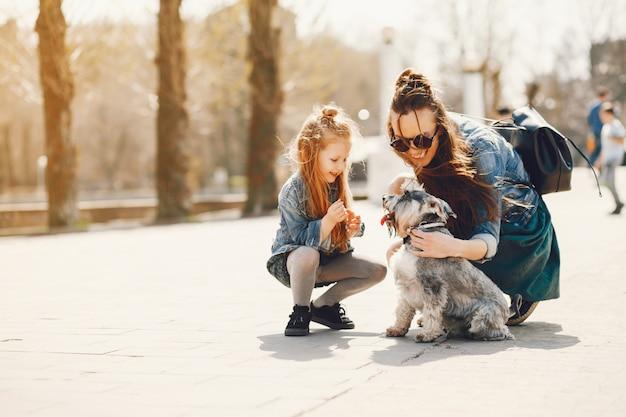 긴 머리를 가진 세련된 어머니와 그녀의 작은 귀여운 딸과 함께 노는 청바지 재킷