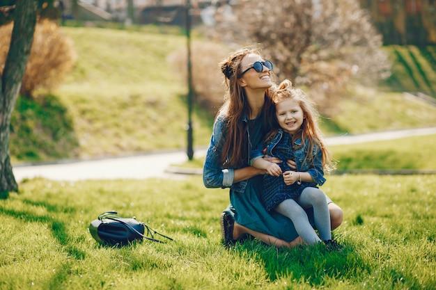 Madre alla moda con i capelli lunghi e una giacca di jeans che giocano con la sua piccola e carina figlia