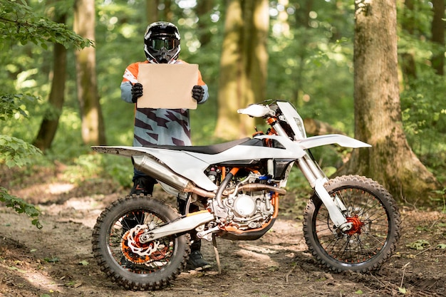 Stylish motorbike rider holding cardboard sign