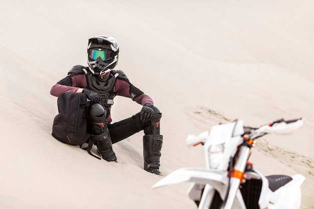 Stylish motorbike rider relaxing in the desert