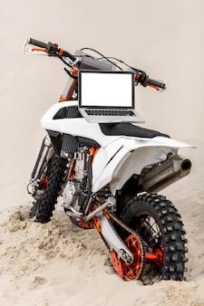 砂漠の上部にラップトップを備えたスタイリッシュなバイク