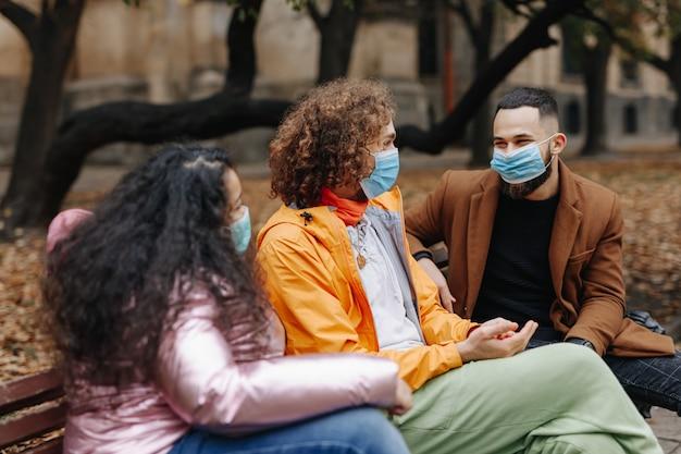 屋外の木製ベンチに座って話している保護フェイスマスクを身に着けているスタイリッシュな多文化の人々。コロナウイルスの概念。