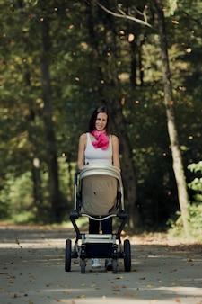緑豊かな緑の木々の間を田舎道に沿ってベビーカーを押すスタイリッシュなママ